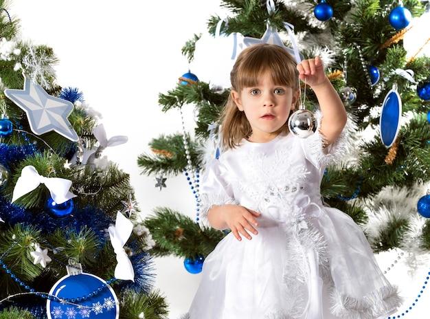 파란색 장난감으로 장식 된 두 개의 새 해 나무의 배경에 대해 포즈를 취하는 아름 다운 작은 호기심 소녀의 초상화.