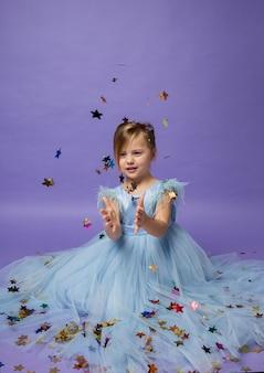 바닥에 앉아 보라색에 화려한 색종이 별을 잡는 파란색 공주 드레스에 아름다운 어린 소녀의 초상화