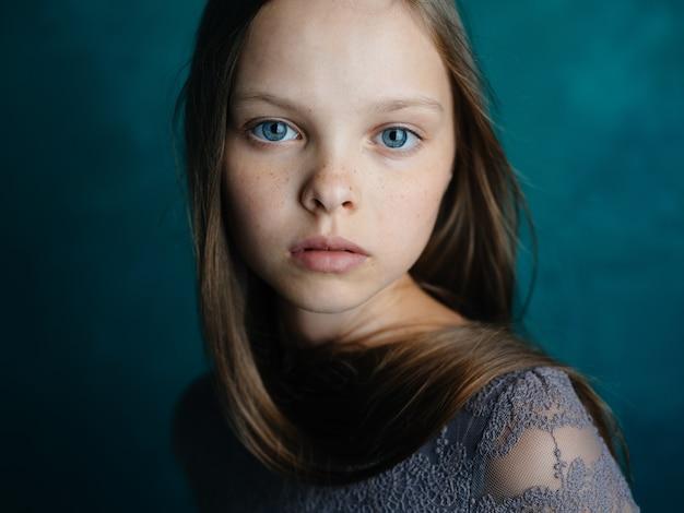 Портрет красивой маленькой девочки в сером платье на бирюзовом фоне и голубыми глазами