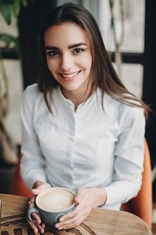 카페에 앉아 점심 시간에 그녀의 손에 커피 한잔과 함께 카메라를 보면서 웃 고 아름 다운 긴 머리 비즈니스 여자의 초상화.