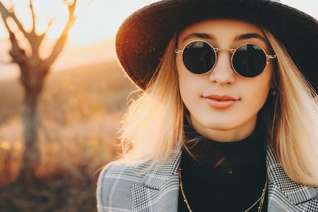 帽子とサングラスを身に着けている美しい長髪の女性の肖像画は、彼女の休暇中に新しい場所を探索しながら、夕日に向かって笑顔のカメラをのぞき込んでいます。