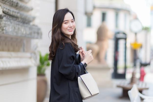 笑顔のウォーキングバッグを運ぶ黒いコートを着た美しい長髪のアジアの女性の肖像画