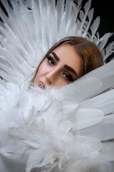 白い翼を持つ美しいモデルの肖像画。背景が黒