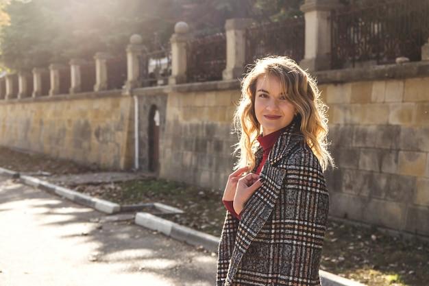 Портрет красивой современной девушки с белокурыми волнистыми волосами в осеннем пальто в солнечном свете.