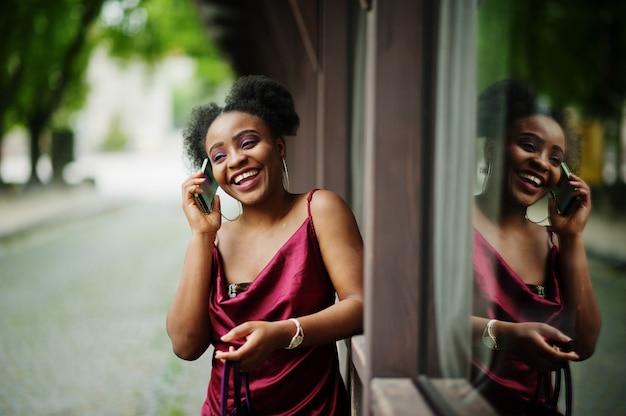 アフロ髪の美しい自然な若いアフリカの女性の肖像画。携帯電話と赤い絹のドレスの黒のモデル。