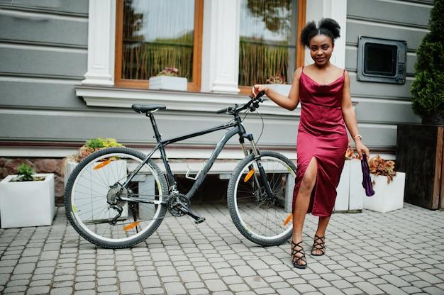アフロ髪の美しい自然な若いアフリカの女性の肖像画。マウンテンバイクと赤い絹のドレスの黒のモデル。