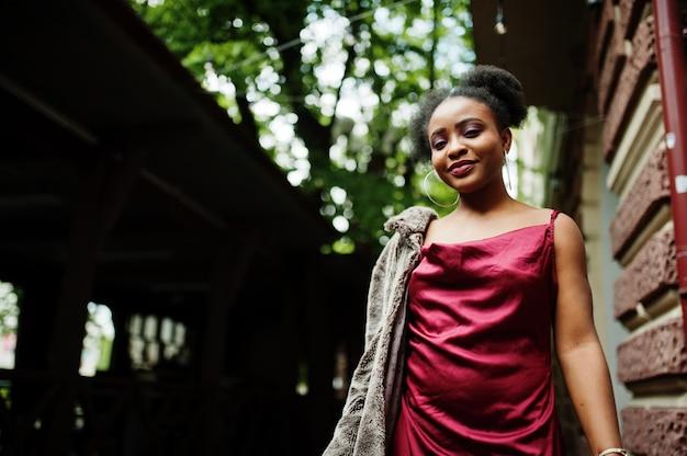 아프리카 머리를 가진 아름 다운 자연 젊은 아프리카 여자의 초상화. 빨간 실크 드레스를 입은 블랙 모델.
