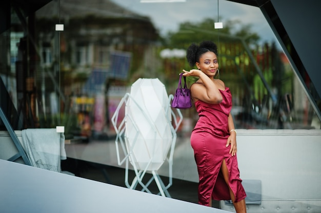 アフロ髪の美しい自然な若いアフリカの女性の肖像画。赤い絹のドレスの黒いモデル。