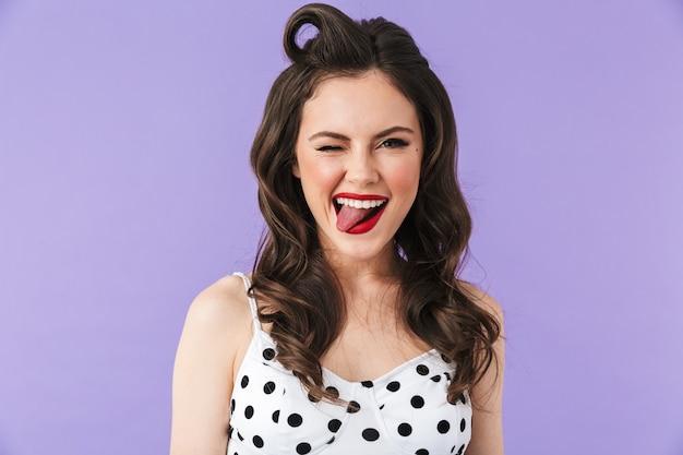 Портрет красивой девушки в стиле пин-ап с ярким макияжем, стоящей изолированно над фиолетовой стеной, аплодируя, празднуя