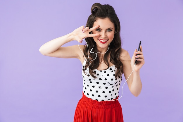 Портрет красивой девушки в стиле пин-ап с ярким макияжем, стоящей изолированно над фиолетовой стеной и слушающей музыку в наушниках и мобильном телефоне