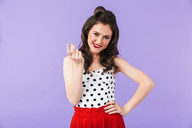 Портрет красивой девушки пин ап с ярким макияжем, стоящей изолированно над фиолетовой стеной и позирующей