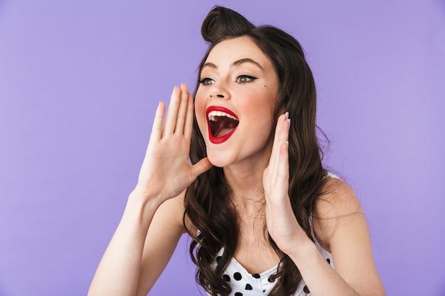Портрет красивой девушки в стиле пин-ап с ярким макияжем, стоящей изолированно над фиолетовой стеной и громко кричащей