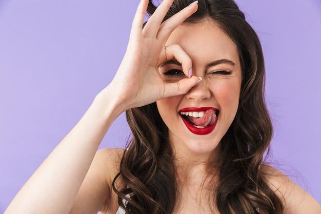 Портрет красивой девушки в стиле пин-ап с ярким макияжем, стоящей изолированно над фиолетовой стеной, показывая хорошо