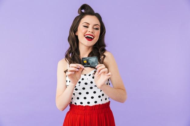 Портрет красивой девушки в стиле пин-ап с ярким макияжем, стоящей изолированно над фиолетовой стеной и показывающей пластиковую кредитную карту