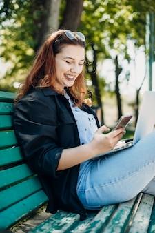 彼女のスマートフォンの笑顔を見ながら彼女の足にラップトップを持って公園のベンチに座っている美しいプラスサイズの女性の肖像画。