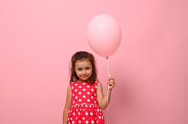 美しいかなりゴージャスな愛らしい4歳の誕生日の女の子、水玉模様のドレスを着た子供、ピンクの風船を持って、広告用のコピースペースでピンクの背景の上に分離されたの肖像画。