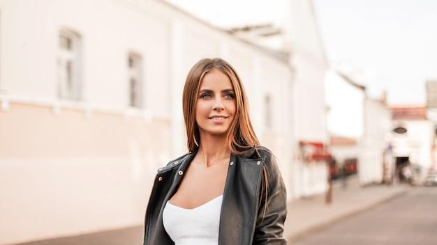 흰색 우아한 상단에 세련된 블랙 가죽 재킷에 갈색 머리를 가진 자연스러운 메이크업으로 귀여운 미소로 아름다운 예쁜 젊은 여자의 초상화. 매력적인 행복 한 여자는 도시 거리에 산책