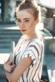 街の夕日に対してラップトップとスマートフォンを保持しながらカメラを真剣に見ているそばかすのある美しい赤い髪の女性の肖像画。