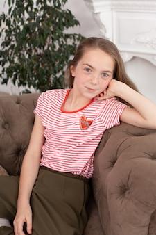 美しい赤毛の十代の少女の肖像画。ソファに座って、笑顔とカメラ目線のかわいい女の子