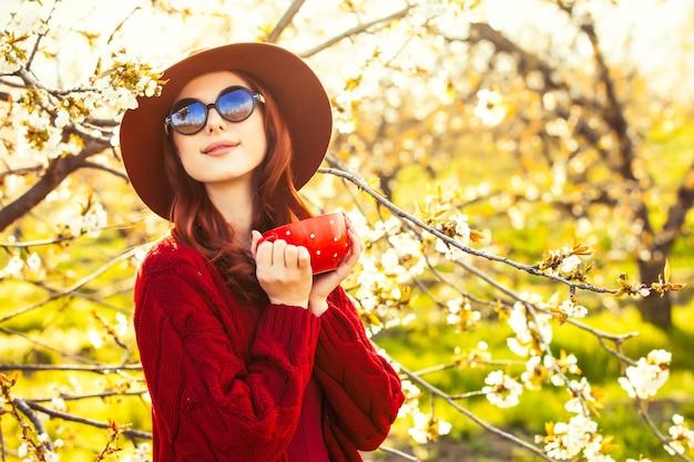 일몰에 봄 시간에 꽃 사과 나무 정원에서 컵과 빨간 스웨터와 모자에 아름 다운 빨간 머리 여자의 초상화.