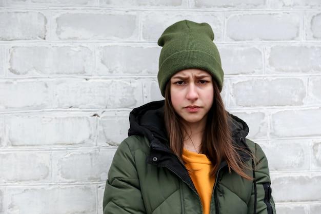 Портрет красивой грустной девочки в желтом свитере и хаки шляпе, которая стоит около белой кирпичной стены. концепция эмоций и копирование пространства
