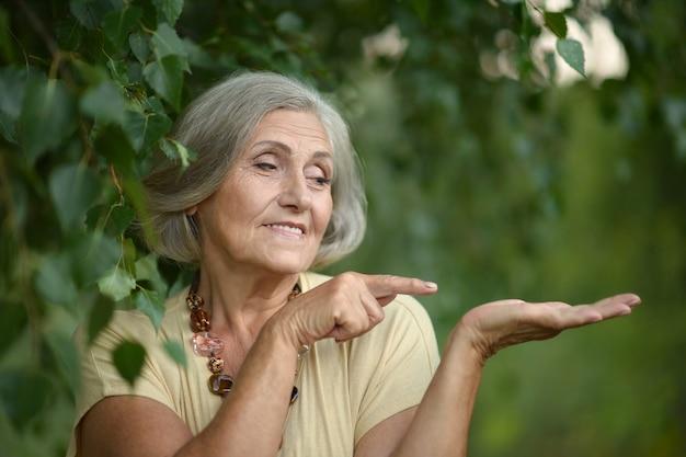 Портрет красивой пожилой женщины в зеленом парке, указывающей на пустой copyspace