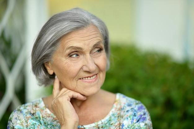 Портрет красивой пожилой женщины в зеленом парке