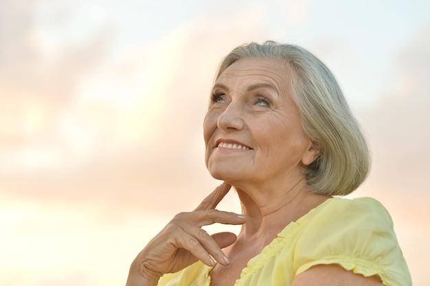 Портрет красивой пожилой женщины на фоне неба