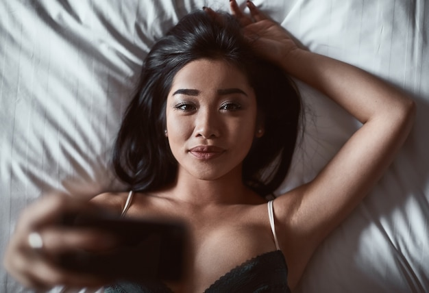 Портрет красивой чувственной азиатской женщины в нижнем белье, лежащей на кровати с телефоном в руке.