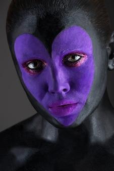 Портрет красивой чувственной женщины с необычным боди-артом с черной кожей и цветными глазами и губами