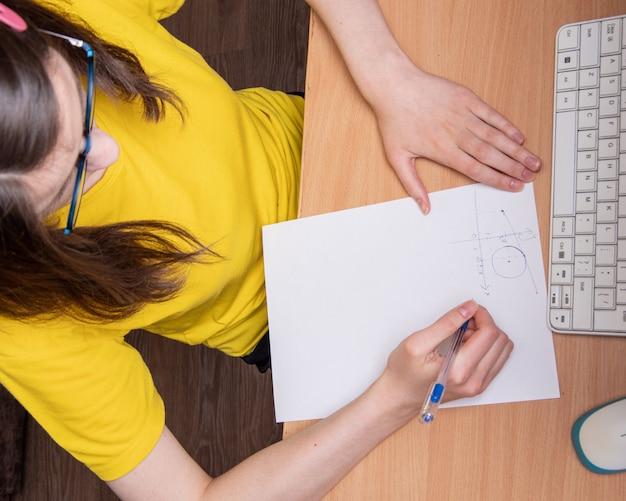 Портрет красивой серьезной кавказской девушки в желтой футболке, пишет график, работает дома, заочное обучение.
