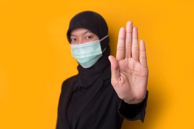 フェイスマスクを身に着けている美しい深刻な若いイスラム教徒の女性の肖像画