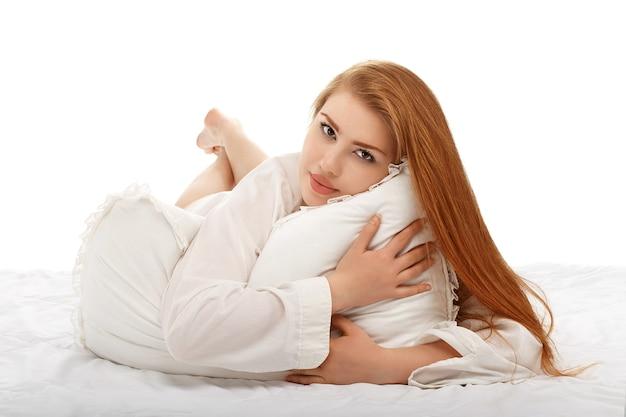 白で隔離の男のシャツを着てベッドに横たわっている美しいセクシーな女の子の肖像画
