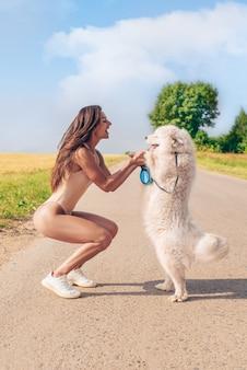 Портрет красивой сексуальной женщины в боди гуляет с собакой. концепция любви, семьи и дружбы. смешанная техника