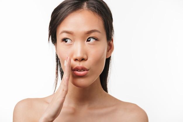 白い壁に隔離されたポーズ健康な肌を持つ美しいショックを受けたアジアの若いきれいな女性の肖像画