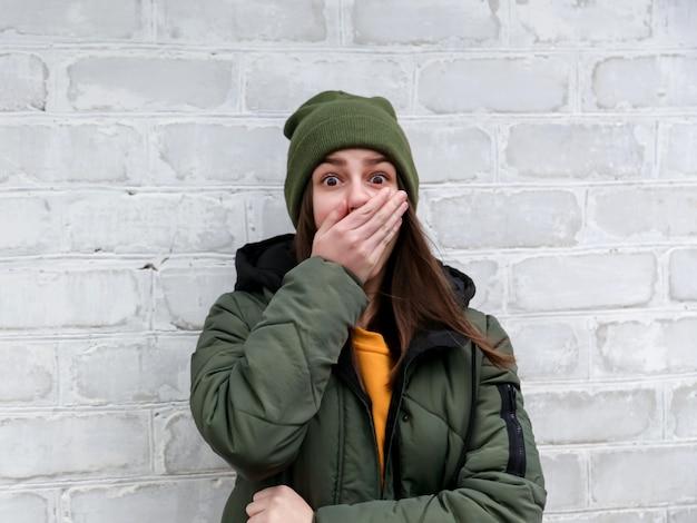 Портрет красивой потрясенной девочки, которая закрывает рот рукой в желтом свитере и хаки шляпе, которая стоит около белой кирпичной стены. концепция эмоций.