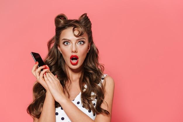 Портрет красивой потрясенной молодой девушки в стиле кинозвезды в платье, стоящей изолированно и держащей мобильный телефон