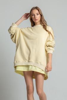 長い黄色のスウェットシャツで美しいスラブの若い女性の肖像画