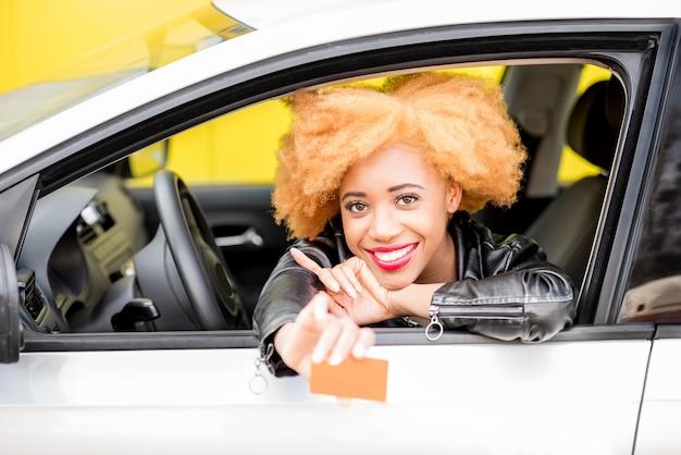 黄色の背景の上の車に座っている空白のカードを示す革のジャケットの美しい笑顔のアフリカの女性の肖像画