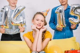 Portrait of a beautiful smiling girl sitting in front of boys holding numeral 14 and 15 foil balloons