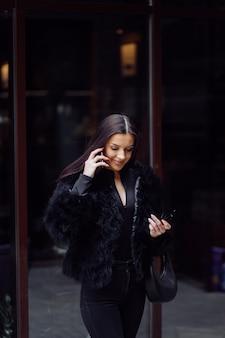 黒を身に着けている長い黒髪の美しい笑顔の女の子の肖像画。携帯電話を使用して若い女性