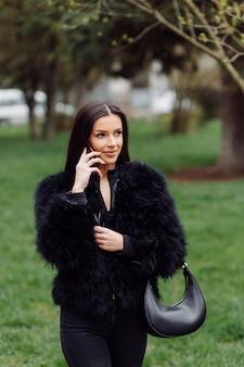 검은 색을 입고 긴 검은 머리를 가진 아름 다운 웃는 소녀의 초상화. 휴대 전화를 사용하는 젊은 여자