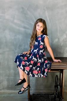 美しい笑顔の少女の肖像画。コピースペースと灰色の壁に木製の古いミシンに座っている女の子