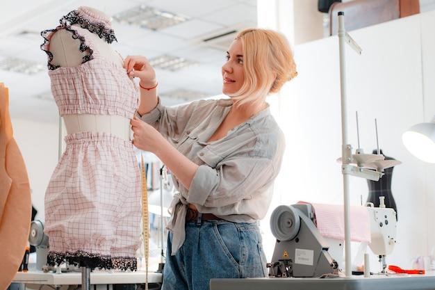 デザイナーの服を着たマネキンの横に立っている測定テープと美しい笑顔の針子の肖像画