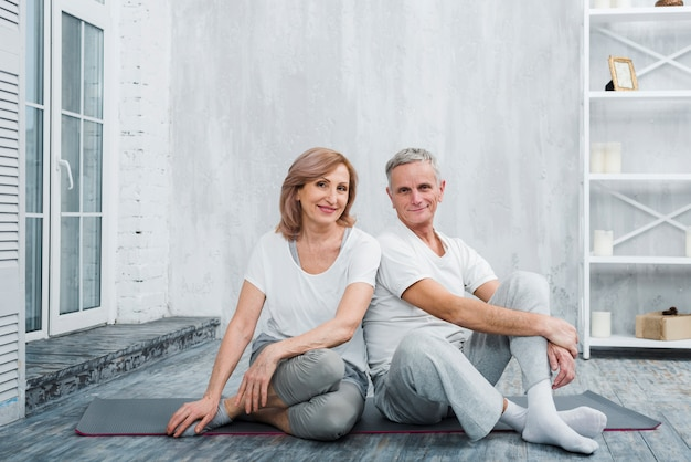 自宅でヨガマットの上に座って美しい笑顔の年配のカップルの肖像画