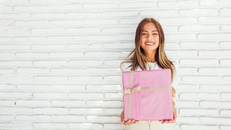 Portrait of a beautiful smiling woman holding pink gift box against brick wall