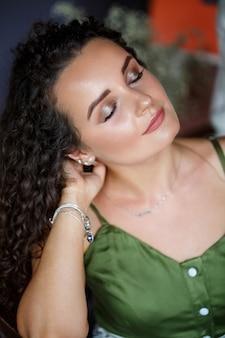 Портрет красивой улыбающейся женщины европейской внешности в платье с прической кудрями. мода и красота