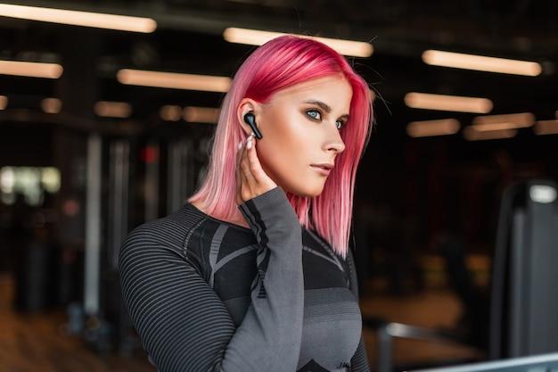 Портрет красивой спортивной женщины с розовыми волосами, бегущей и слушающей музыку через беспроводные наушники в спортивном зале