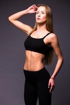 灰色の壁に腰に手を持って美しいスポーツ女性の肖像画