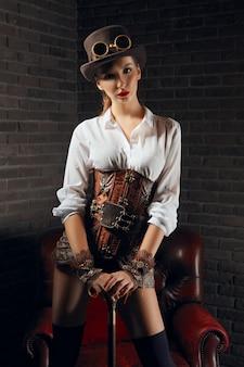 Портрет красивой девушки стимпанк в нижнем белье и чулки, шляпа и очки.